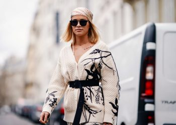 """PARIS, FRANCE - MARCH 02: Julia Kuczynska """"Maffashion"""" wears a bandanna from Gucci, a white wool jacket with print depicting nature, white pants, a Prada bag, white boots, outside Elie Saab, during Paris Fashion Week Womenswear Fall/Winter 2019/2020, on March 02, 2019 in Paris, France. (Photo by Edward Berthelot/Getty Images)"""