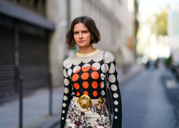 PARIS, FRANCE - OCTOBER 04: Marta Cygan wears a wool pullover with printed black orange and white dots, a belt with golden buckle, a white floral print colored skirt, a metallic bag, outside Paco Rabanne, during Paris Fashion Week - Womenswear Spring Summer 2021, on October 04, 2020 in Paris, France. (Photo by Edward Berthelot/Getty Images)