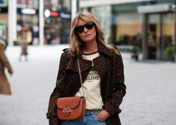 DUESSELDORF, GERMANY - DECEMBER 10: Influencer Gitta Banko wearing a dark brown trenchcoat with 70's triomphe print by Celine, a cream colored logo print t-shirt by Celine, a cognac colored chain bag with gold  triomphe details by Celine, light blue slim fit denim jeans by AG Jeans and sunglasses by Bottega Veneta during a street style shooting on December 10, 2020 at Breuninger in Duesseldorf, Germany. (Photo by Streetstyleshooters/Getty Images)