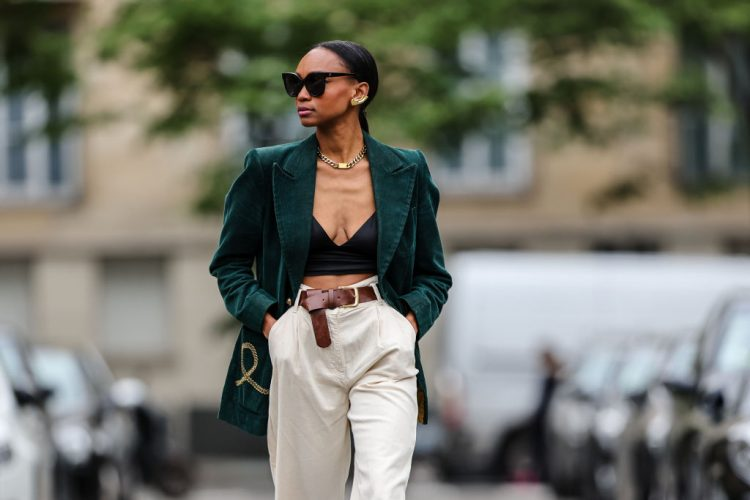PARIS, FRANCE - MAY 20: Emilie Joseph wears a gold large chain necklace, a black silk V-neck crop top top / satin bralette, a dark green velvet long blazer vintage jacket with epaulets, a brown shiny leather belt / Light corduroy fitted blazer with notched collar in emerald green , white latte flared dad pants, on May 20, 2021 in Paris, France. (Photo by Edward Berthelot/Getty Images)