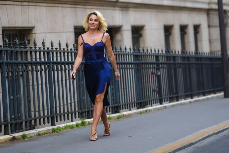 PARIS, FRANCE - JULY 07: A guest wears silver earrings, a silver pendant necklace, a royal blue dress made of a lace tank-top and a ruffled asymmetric long skirt, a black shiny leather wallet, black leather strappy pumps heels shoes, outside Zuhair Murad, during Paris Fashion Week - Haute Couture Fall/Winter 2021/2022, on July 07, 2021 in Paris, France. (Photo by Edward Berthelot/Getty Images)